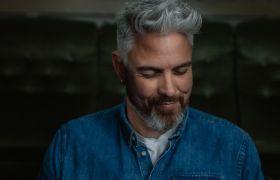 Portrett av forfatter Trygve Skaug i blå dongeriskjorte, men grått skjegg og hår, mot mørk bakgrunn.