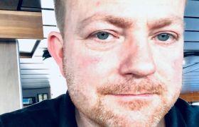 Bas/nettmann Jermund Skår er avbildet fra brystet og opp, iført mørk skjorte med rød logo. Han er avbildet i styrehuset på en båt.