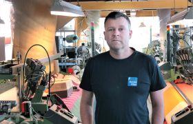 Fagoperatør i veving Morten Felgenhauer står i produksjonslokalet med vever i bakgrunnen.