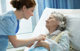 Geriater prater med eldre kvinne.