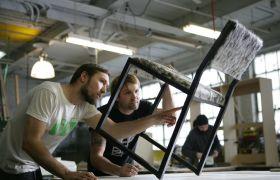 Industritapetserere som inspiserer en stol.
