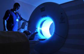 Onkologen fører en person inn i ei strålemaskin