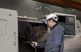 CNC-operatør jobber ved ei CNC-maskin