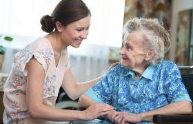 Kvinnelig hjemmehjelper snakker og smiler til eldre kvinne.