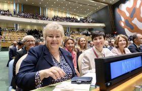 Bilde av Statsminister Erna Solberg og Utenriksminister Ine Marie Eriksen Søreide sit i ein sal saman med fleire andre menneske.
