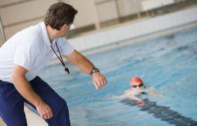 Idrettstrener sekunderer svømmer i bassenget