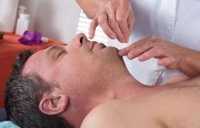 Akupunktør setter nåler i ansiktet på en mann
