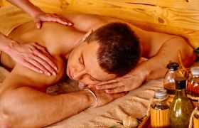 Mann mottar massasje fra aromaterapeut.