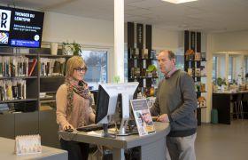 Bibliotekar og bruker ved utlånsskranke i Nes kommune i Akershus´ nye bibliotek, 2012.