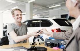 Bilselger overleverer nøkler til kjøper av ny bil.
