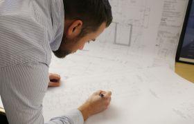 Byggingeniør sjekkar arkitekttegninger.