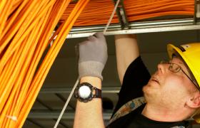 Elektrikar i arbeid, stripser fast kabler