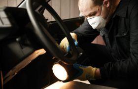Etterforsker samler bevis fra en bil.
