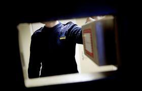 Fengselsbetjent synlig gjennom åpen luke fra innsiden av fengselscelle.