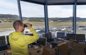 En mann i et flytårn ser ut mot flystripa gjennom en kikkert.