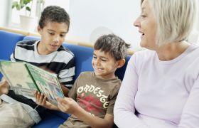 Illustrasjonsbilde av en kvinne som sitter sammen med to barn som ser i ei bok.