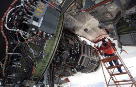 Flystrukturmekanikeren står i en stige og skrur på en motor på et passasjerfly
