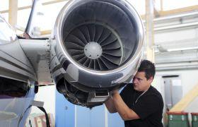 Flysystemmekaniker jobber på en propelldel.
