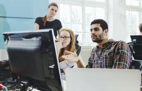 To forretningsutviklere diskuterer og ser på en skjerm