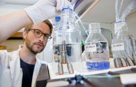 Mannleg forskar dypper slangar i reagensglas.