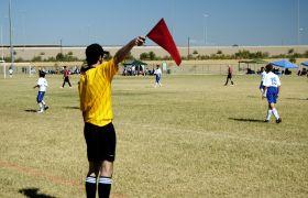 Fotballdommer holder opp et flagg i en fotballkamp.