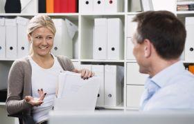 To kollegaer snakker sammen på et kontor