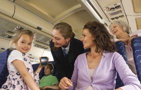 En liten jente holder smilende opp en mobiltelefon. Kabinpersonale, mor, bestemor og bror ser på i bakgrunnen.