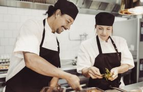 Kjøkkensjef og kokk i arbeid på kjøkken.