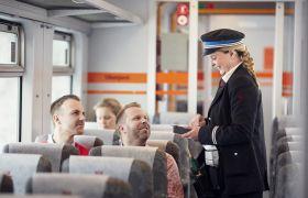 Illustrasjonsbilde av en konduktør som betjener reisende på et tog.