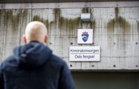 """Mann går under skilt kor det står """"Kriminalomsorgen – Oslo fengsel""""."""