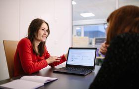 Markedsføringskonsulent viser fram planar på et møte.