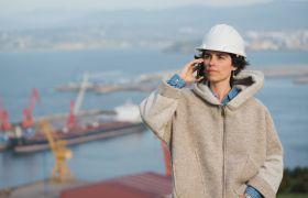Maskinsjef står i hamna og snakker i en mobiltelefon.