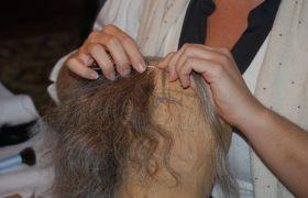 Illustrasjonsbilde av en maskør- og parykkmaker i arbeid med en parykk.