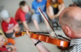 Lærer på musikkskole underviser elevene i å spille fiolin.