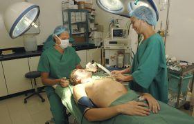 Mannlig pasient på sykeseng blir behandlet av anestesilege og operasjonssykepleier før operasjon.