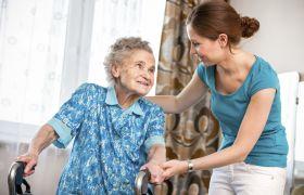Pleiemedarbeider hjelper eldre kvinne