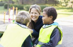 SFO-leder i samtale med barn i skolegården.