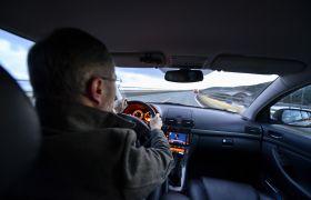 Sjåfør bak rattet i personbil.