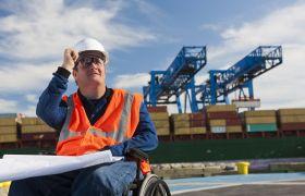 Mannlig skipsmegler i rullestol studerer logistikkplaner på kaia ved et fraktskip.