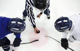 En ishockeydommer dropper pucken mellom to spillere.