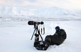 Fotograf tar bilder med lang tele under vinterlige forhold på Svalbard.