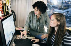 Voksen dame og ung dame jobber sammen på datamaskin