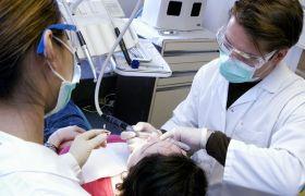 Tannlege polerer tennene til en pasient, mens en tannhelsesekretær holder et beger med slipepasta som brukes i poleringen.