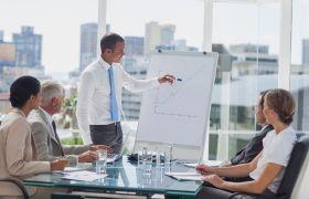 Ein mann står og peiker på ein graf som er på et stort ark, mens han står framfor sine fire kollegaer.