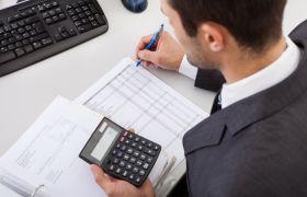 Regnskapsfører sitter med en kalkulator i den ene hånden og ei penn i den andre, og noterer på et ark.