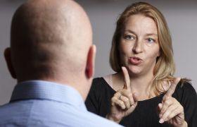 Kvinnelig tolk prater med lyd og bevegelser.