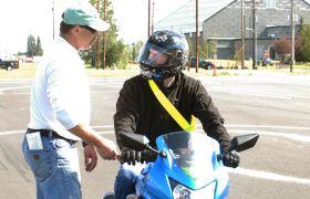Trafikklærer underviser motorsyklist.