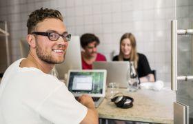 Webdesigner foran dataskjerm med kolleger i bakgrunnen.
