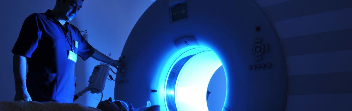 Onkologen fører ein person inn i ei strålemaskin