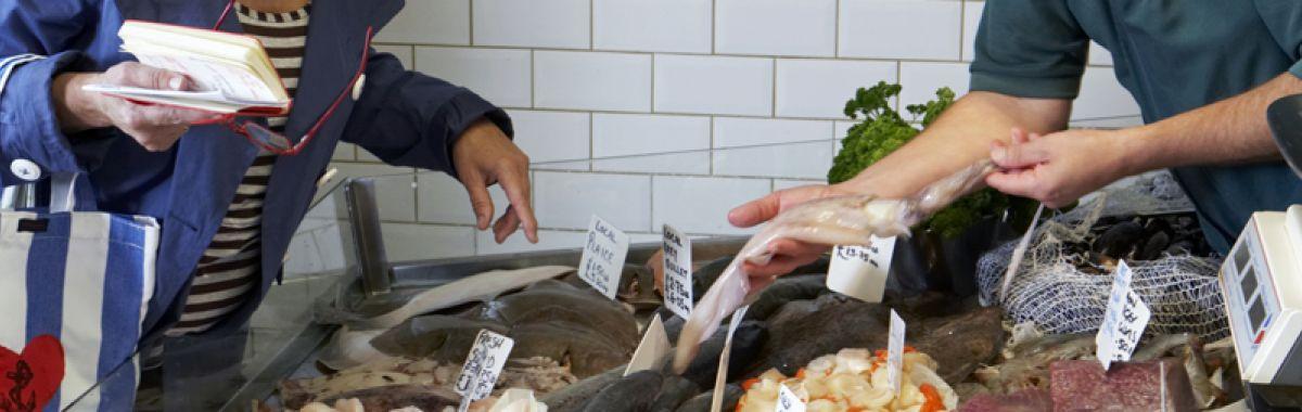 Kvinne som kjøper fisk av en mannlig fiskehandler